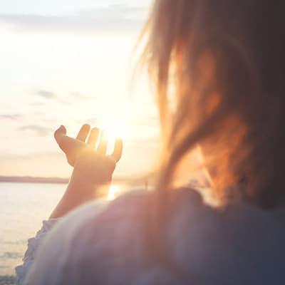 Une femme zen devant un coucher de soleil